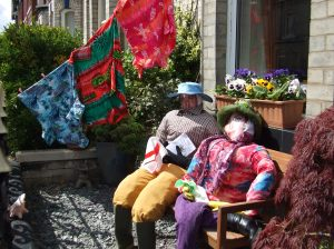Two scarecrows sitting on a bench